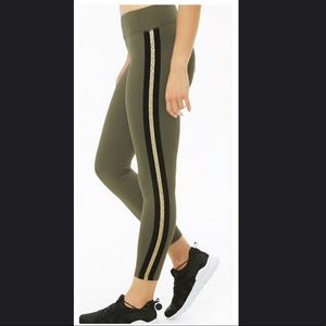 Green leggings with a gold and black stripe